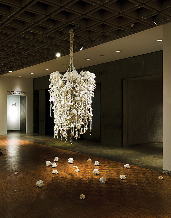 A white sculpture hangs from the ceiling in a gallery.