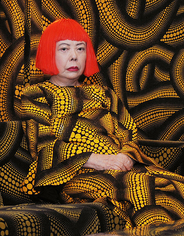 The artist Yayoi Kusama with her signature orange wig, wearing a print that is repeated in the backdrop.