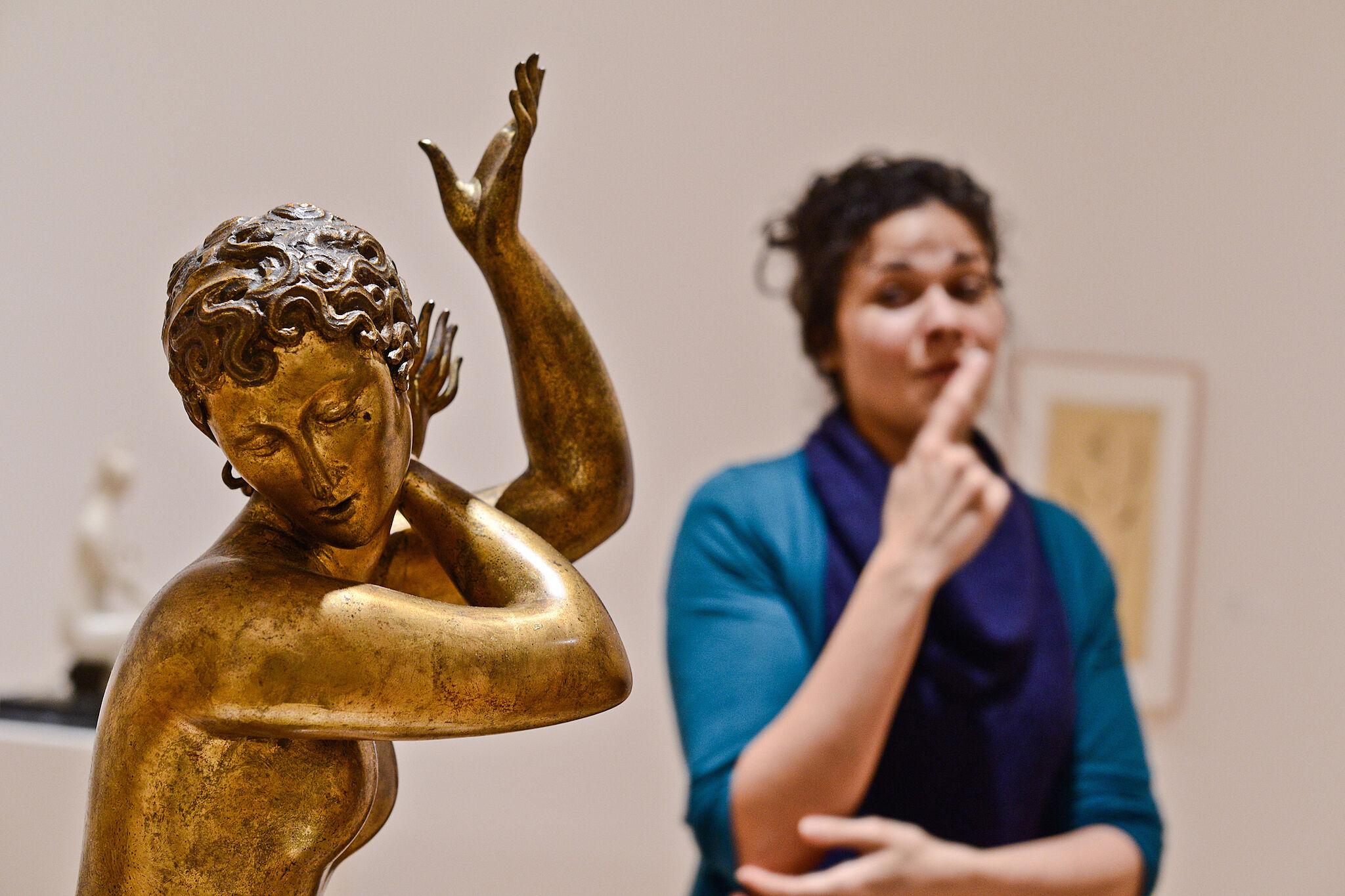 A woman standing next to a sculpture.
