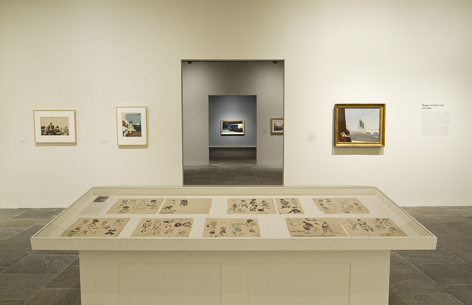 Sketches displayed in cases with paintings just beyond them.