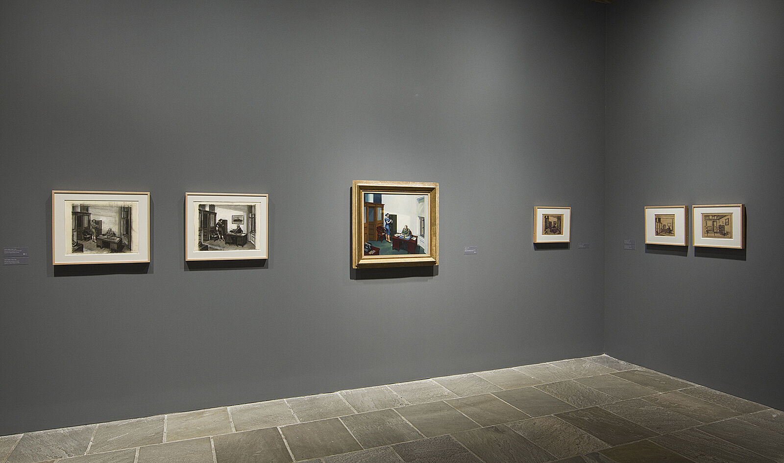 Painting and drawings hang against gray wall.