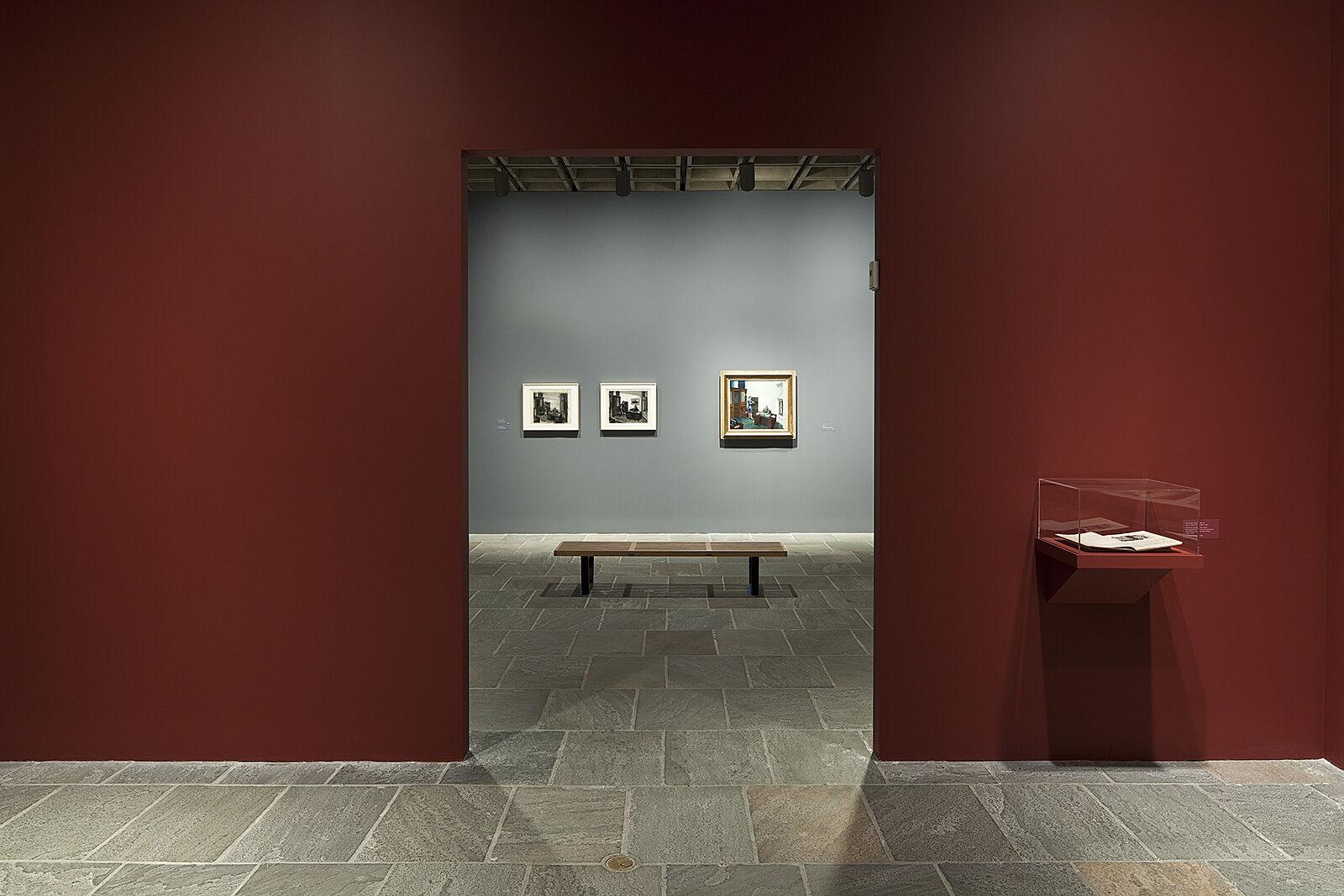Doorway of exhibition with maroon walls.