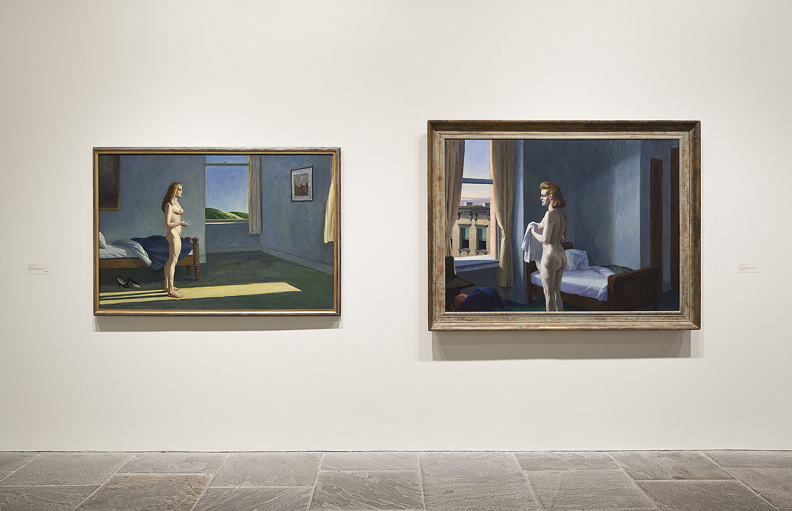 Paintings of nudes hang side by side.