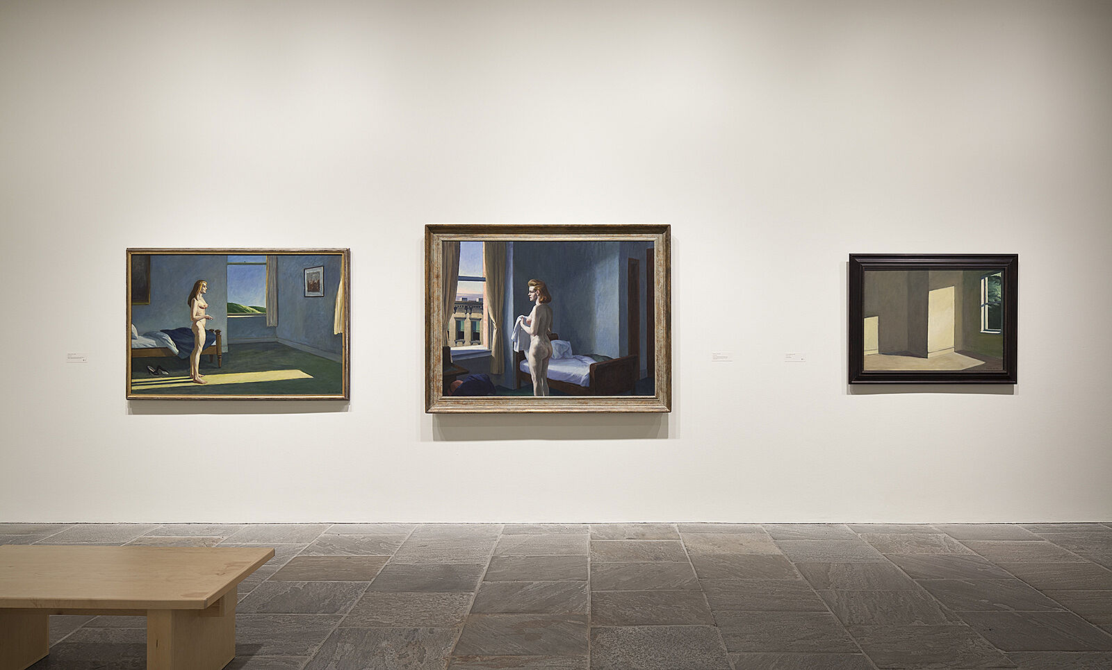 Three paintings hang beside each other in exhibition.