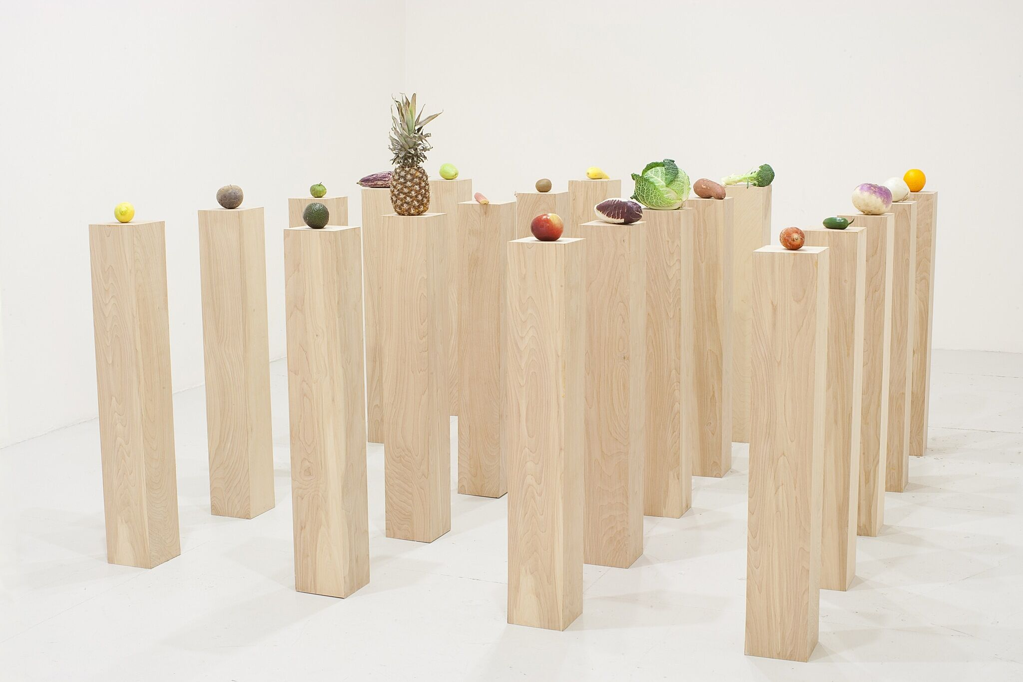 A photo of various fruits and vegetables perched on wood plinths