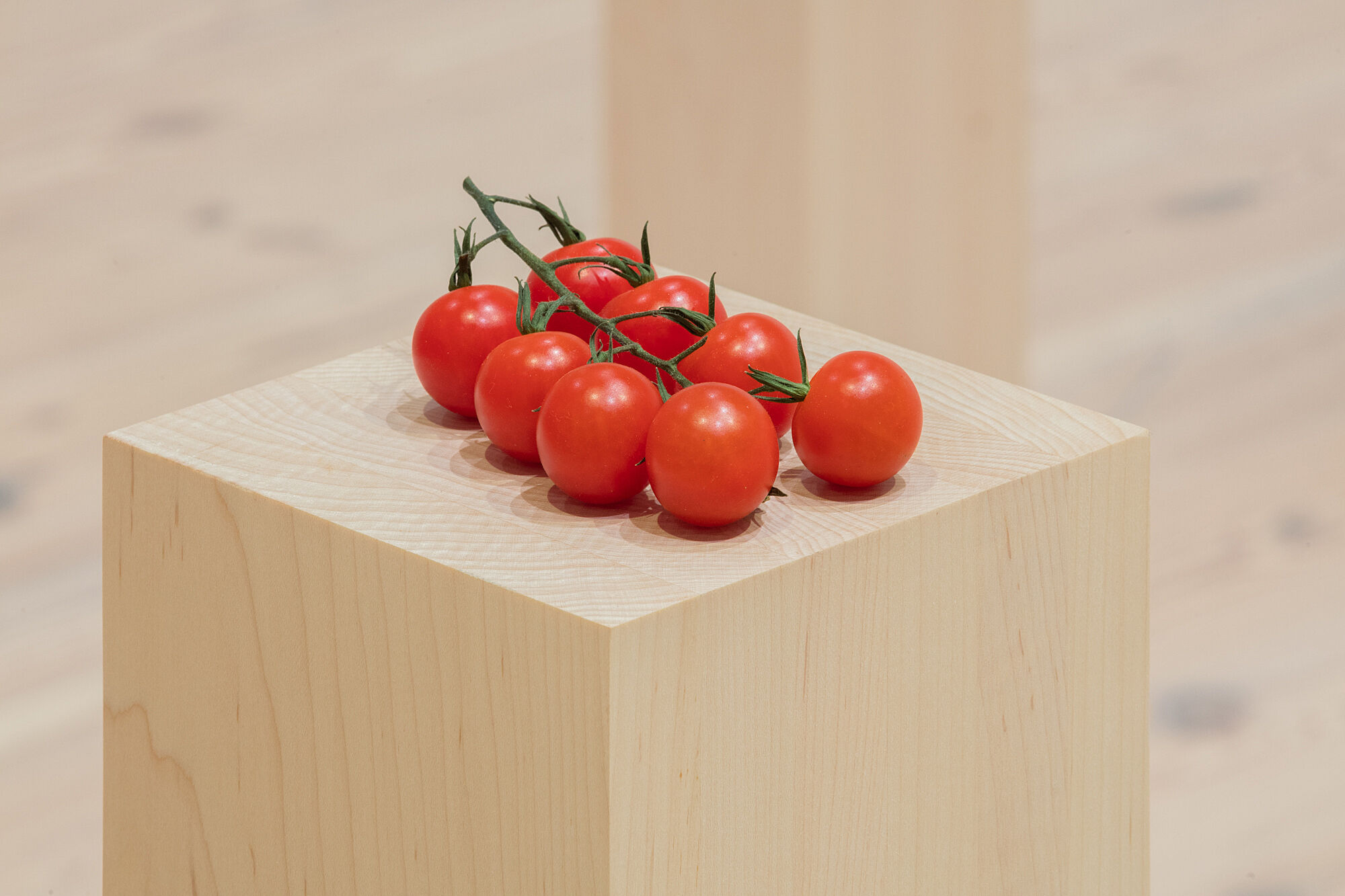 A photo of cherry tomatoes on a plinth.